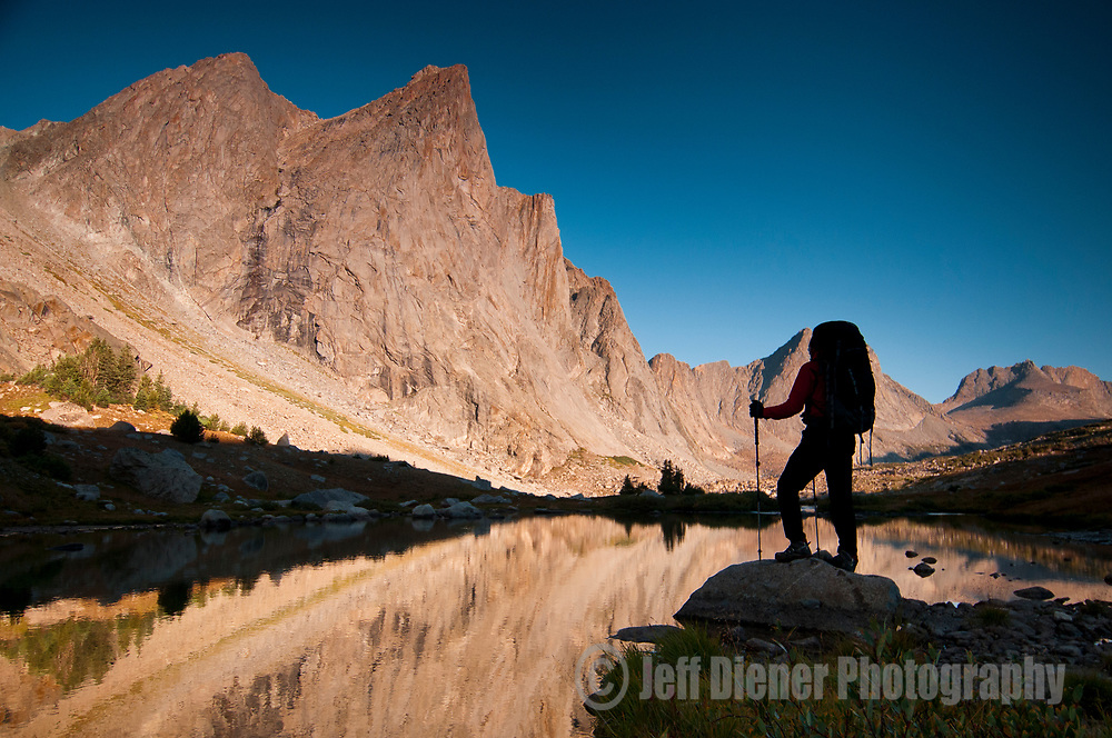 A young man views the high peaks at sunrise in the Wind River Mountains, Wyoming.