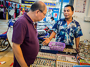 02 JUNE 2015 - KULAI, JOHORE, MALAYSIA: MOHAMMAD AYUB, a Rohingya from Sittwe, Myanmar, talks to a Malaysian man shopping for gems in Ayub's shop in a mall in Kulai, Malaysia. Ayub left Myanmar when he was 13, in 1989, with just a friend but no family members and ended up in Kulai where he started a successful gems and jewelry business. The UN says the Rohingya, a Muslim minority in western Myanmar, are the most persecuted ethnic minority in the world. The government of Myanmar insists the Rohingya are illegal immigrants from Bangladesh and has refused to grant them citizenship. Most of the Rohingya in Myanmar have been confined to Internal Displaced Persons camp in Rakhine state, bordering Bangladesh. Thousands of Rohingya have fled Myanmar and settled in Malaysia. Most fled on small fishing trawlers. There are about 1,500 Rohingya in the town of Kulai, in the Malaysian state of Johore. Only about 500 of them have been granted official refugee status by the UN High Commissioner for Refugees. The rest live under the radar, relying on gifts from their community and taking menial jobs to make ends meet. They face harassment from Malaysian police who, the Rohingya say, extort bribes from them.     PHOTO BY JACK KURTZ