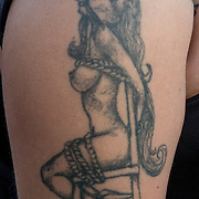 Bondage tattoo on her shoulder and arm, size view of nude female tied to chair.<br /> <br /> Tattoos are no longer just a male thing, young women are just as likely to get a tattoo as males. <br /> <br /> Body art or tattoos has entered the mainstream it is no longer considered a weird kind of subculture.<br /> <br /> &quot;According to a 2006 Pew survey, 40% of Americans between the ages of 26 and 40 have been tattooed&quot;.