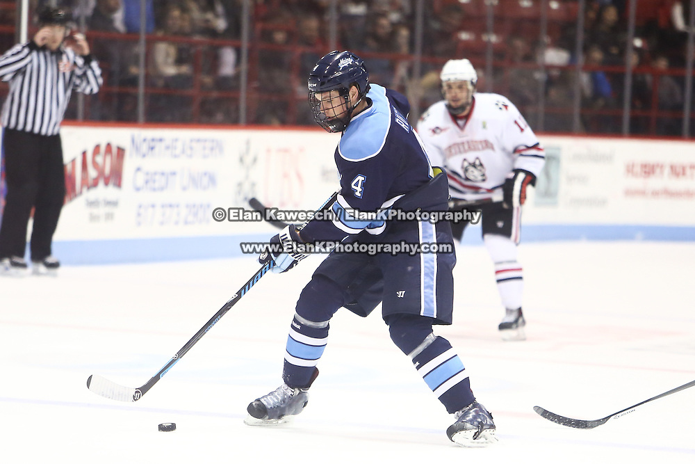 Jake Rutt #4 of the Maine Black Bears with the puck during the game at Matthews Arena on February 22, 2014 in Boston, Massachusetts. (Photo by Elan Kawesch)