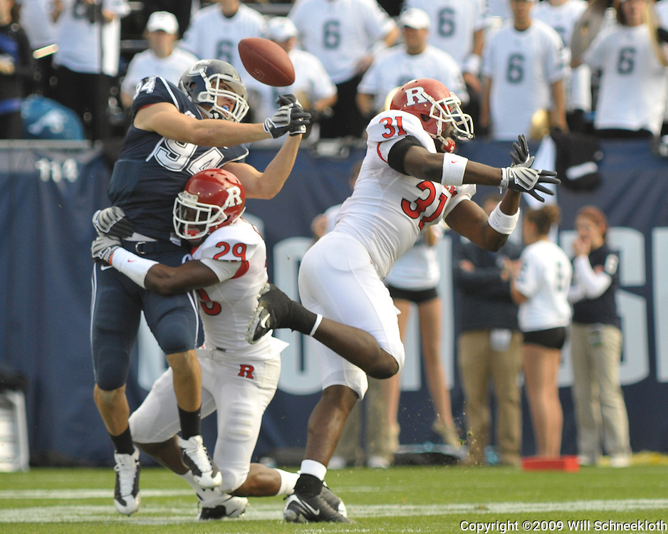 Oct 31, 2009; East Hartford, CT, USA; Rutgers cornerback Zaire Kitchen (29) and defensive end George Johnson (31) break up Connecticut tight end Ryan Griffin's (94) reception attempt during first half Big East NCAA football action between Rutgers and Connecticut at Rentschler Field.