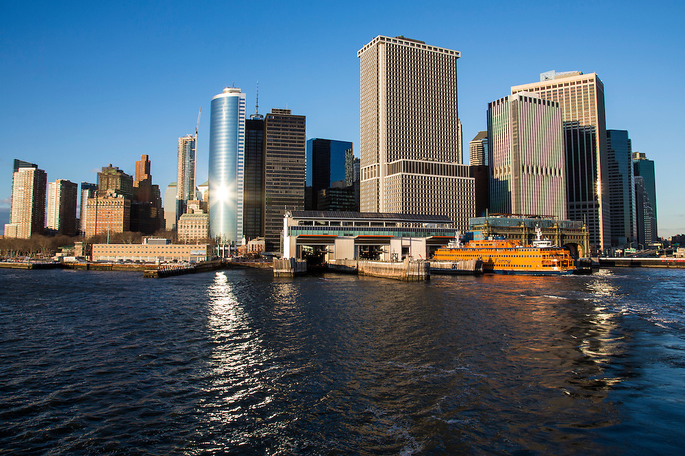 A Staten Island Ferry waits in the Whitehall Terminal in Lower Manhattan, New York City, New York, United States of America. Sunlight reflects off 17 State Street building in the heart of the Financial District of Manhattan and famous for its distinct curved facade.  (photo by Andrew Aitchison / In pictures via Getty Images)