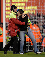 Photo: Daniel Hambury.<br />Arsenal v Cardiff City. The FA Cup. 07/01/2006.<br />A Cardiff fan runs onto the pitch and is tackled by stewards.