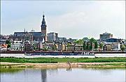 Nederland, The Netherlands, Nijmegen 22-7-2016Een binnenvaartschip vaart over de rivier de waal naar Duitsland. Op de achtergrond het panorama van de stad met de st. stevenskerk, stevenstoren . op de voorgrond het water van de nevengeul, spiegelwaal .Onlosmakelijk met de vierdaagse, 4daagse, zijn in Nijmegen de vierdaagse feesten, de zomerfeesten.Recreatie, ontspanning, cultuur, dans, theater en muziek in de binnenstad. Nijmegen summer capital of hollandTalrijke podia staat een keur aan artiesten, voor elk wat wils. Een week lang elke avond komen ruim honderdduizend bezoekers naar de stad. De politie heeft inmiddels grote ervaring met het spreiden van de mensen, het zgn. crowd control. De vierdaagsefeesten zijn het grootste evenement van Nederland en verbonden met de wandelvierdaagse. Foto: Flip Franssen