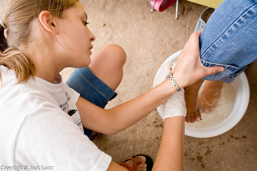 16 JULY 2007 -- NOGALES, SONORA, MEXICO: ANDREA LEONARD, a volunteer from Tucson, AZ, with No More Deaths, bathes the blistered feet of a Mexican teenager deported from the US at the No More Deaths aid station near the Mexican port of entry in Nogales, Sonora, Mexico. No More Deaths and the Sonora state government set up the aid station in 2006 to help Mexican immigrants deported from the US from across the US Border Patrol station in Nogales, Arizona. Volunteers at the aid station provide immigrants, many of whom spend days in the desert before being apprehended by the US Border Patrol, with food and water and rudimentary first aid. The immigrants then go back to their homes in Mexico or into Nogales to make another effort at crossing the border. Volunteers said they help between 600 and 1,000 immigrants per day. The program costs about .60¢ per person to operate. So far this year they've helped more than 130,000 people.  Photo by Jack Kurtz