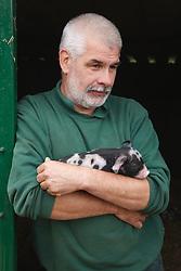 Farmer holding piglets