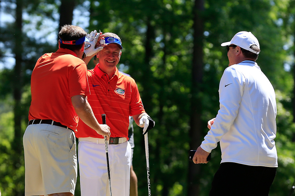 Dan Mullen high fives Judd Davis after getting pranked with an exploding golf ball during the Chick-fil-A Peach Bowl Challenge at the Oconee Golf Course at Reynolds Plantation, Sunday, May 1, 2018, in Greensboro, Georgia. (Paul Abell via Abell Images for Chick-fil-A Peach Bowl Challenge)