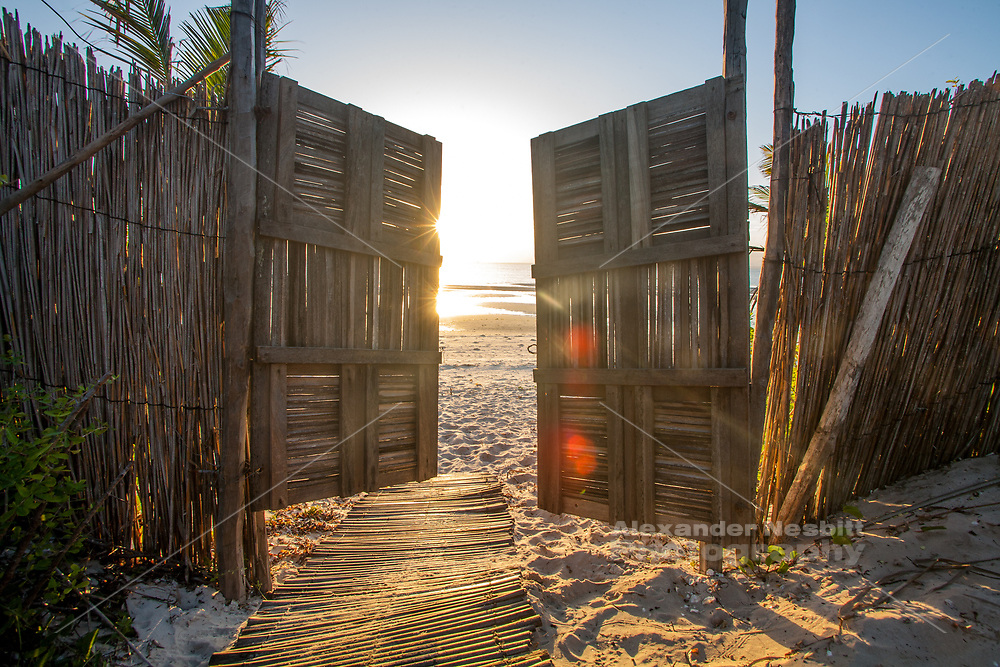 Sunrise emerges throught eh door to the beach, backpaker lodge in Vilankulo Mozambique