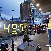 """Nederland, Amsterdam , 1 oktober 2009..Het publiek wacht buiten in de regen op het moment dat de deuren van de Bijenkorf opengaan  voor de koopjes tijdens de eerste dag  van de Drie Dwaze Dagen ..Zanger Jeroen van der Boom van """"de Toppers"""" telt voor de ingang de laatste minuten af. Om 8.00u gaan de deuren open. .Three Crazy Days, annual sale of the Bijenkorf store, promoting bargains."""
