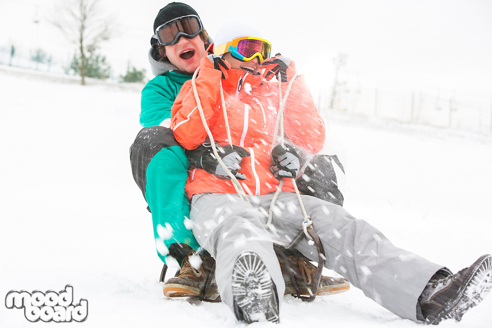 Excited young couple sledding in snow