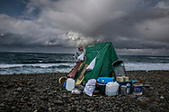 "Local man at his makeshift fishing shelter in a gail wind.  He fishes for ""sake"" (salmon).  When salmon enter fresh water, their health deteriorates and so does their muscle mass people eat.  So, the quality of a salmon caught in the sea versus the river.  Mashike, Hokkaido, Japan"