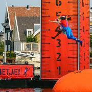 NLD/Huizen/20180706 - Opanem Bommetje 2018, deelnemers gaan van de schans af in het water