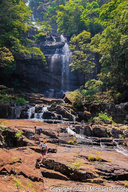 Hikers near the base of Mount Gorongosa, Mozambique. The massive waterfall is like a many-layered wedding cake and this is just the bottom.