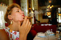 June 1996, Paris, France --- Woman Smoking a Cigar in a French Restaurant --- Image by © Owen Franken