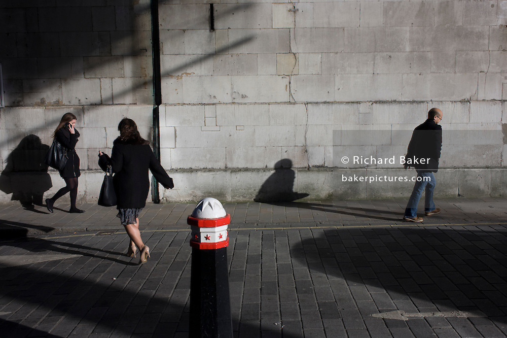 City of London bollard and passers-by shadows on church wall.