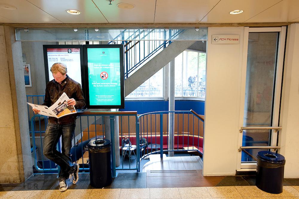 Een student aan de Universiteit van Amsterdam (UvA) leest de Folia, de universiteitskrant.<br /> <br /> A student of the University of Amsterdam is reading the newspaper of the university.