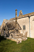 Building exterior of historic church of Saint John, Inglesham, Wiltshire, England, UK 13th century with 15th century churchyard cross