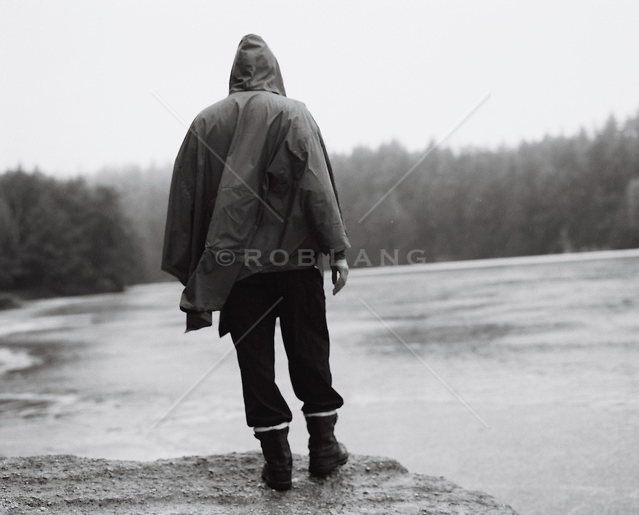 Man in a rain slicker standing on a rock by a lake