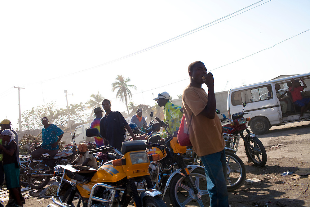 People stand around at a large outdoor market in Port-au-Prince, Haiti.