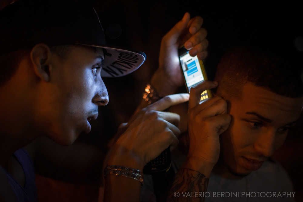 A boy listens to an audio off a smartphone while another keep chatting. Parque  Fe del Valle, Havana, Cuba, on the night of 28 December 2015. The several ways of sharing media that modern devices give is an endless discovery for Cuban that have been cut out of modern technology until 2015. These boys were probably aware of the photographer, but they continued in their activity. This photo was not staged.<br />