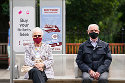 Edinburgh, Scotland, UK. 24 July, 2020. Senior couple sitting at tram stop social distancing themselves and wearing facemasks.  Iain Masterton/Alamy Live News