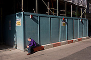 A lone man sits in the sunshine, beneath a conbstruction site hoarding in central London.