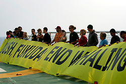 NORTHERN PACIFIC ESPERANZA 16NOV07 - Campaigners aboard the MY Esperanza hold up a banner on the heli deck which reads: 'Bush, Fukuda: End Whaling' off the coast of Japan. The Greenpeace ship 'Esperanza' is currently positioned just outside Japanese territorial waters and will be shadowing the Japanese whaling fleet after it leaves the port of Shimonseki for its passage towards the Antarctic...jre/Photo by GREENPEACE/Jiri Rezac