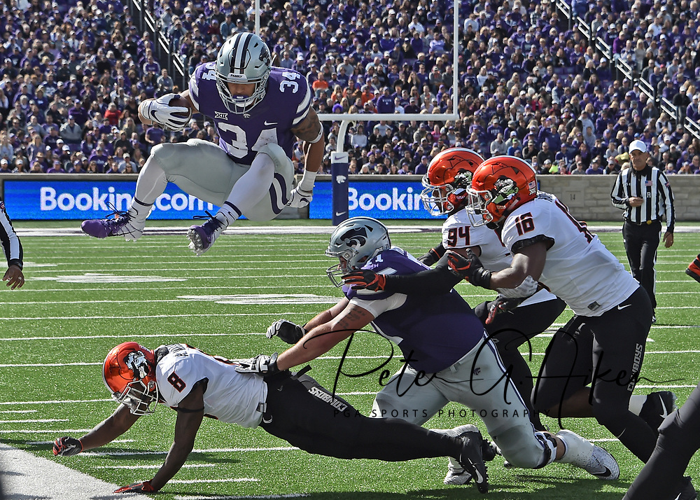 MANHATTAN, KS - OCTOBER 13:  Running back Alex Barnes #34 of the Kansas State Wildcats hurdles over cornerback Rodarius Williams #8 of the Oklahoma State Cowboys to pick up a fist down during the first half on October 13, 2018 at Bill Snyder Family Stadium in Manhattan, Kansas.  (Photo by Peter G. Aiken/Getty Images) *** Local Caption *** Alex Barnes;Rodarius Williams
