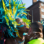 A female dancer licks a security man from his chin and all the way up his face in a very suggestive way. The Notting Hill Carnival has been running since 1966 and is every year attended by up to a million people. The carnival is a mix of amazing dance parades and street parties with a distinct Caribbean feel.