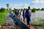 Men from a Moor village walk across a small dam that was built to help retain rain water. Global warming and climate change have caused prolonged drought and erratic rainy seasons across the Sahel in recent years, contributing to food insecurity, poverty and human migration throughout the region. One of the problems with the disrupted cycles of rainy and dry seasons is that when the rains do fall, the precipitation rapidly runs off the parched landscape and very little is retained for crops or absorbed into the water table. Improved water management systems such as this dam help retain rain waters, increase seepage into the water table, improve agricultural yields and extend the planting season, allowing rural communities to better adopt to and mitigate the effects of climate change. <br />