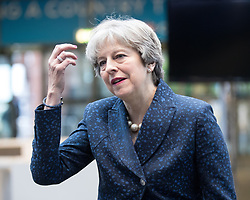 © Licensed to London News Pictures . 02/10/2017. Manchester, UK. Prime Minister THERESA MAY straightens her hair as she enters the conference hall from the wind , at the start of the second day of the Conservative Party Conference at the Manchester Central Convention Centre . Photo credit: Joel Goodman/LNP