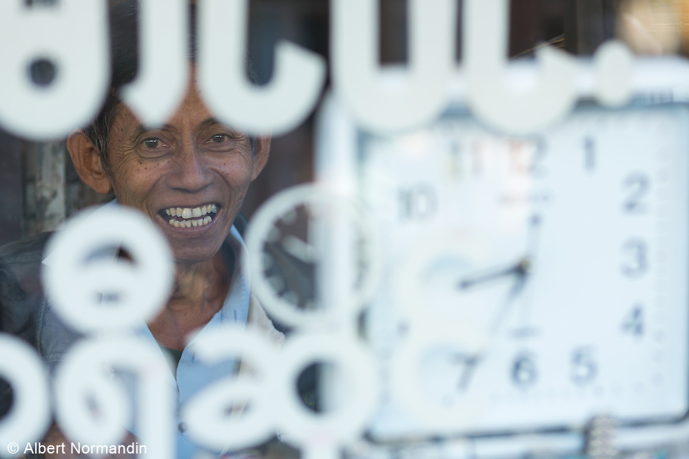 Watch repair man laughing, smiling through window sign in shop, Pyay