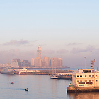 Sunrise in the industrial port of Casablanca, Morocco, with a view of the Hassan II Mosque in the background.