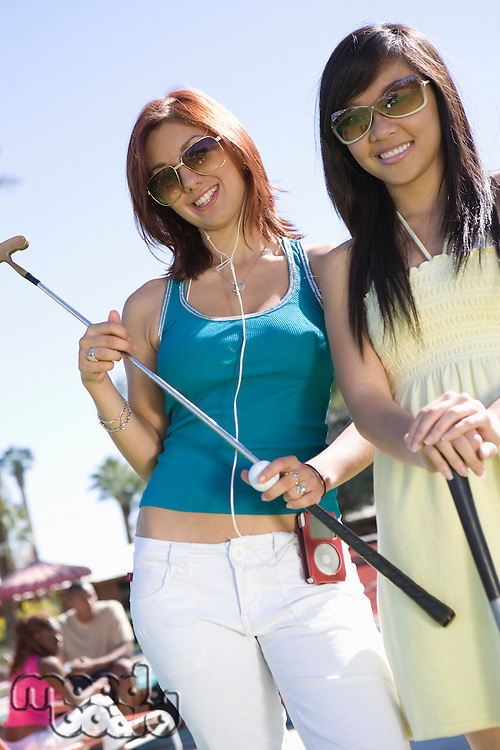 Two Young Women Holding Golf Clubs, Portrait