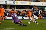 Millwall FC Midfielder Shane Ferguson slots one past Colchester FC Goalkeeper Jamie Jones during the Sky Bet League 1 match between Millwall and Colchester United at The Den, London, England on 21 November 2015. Photo by Andy Walter.