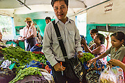 15 JUNE 2013 - YANGON, MYANMAR:  A conductor collects tickets and fares on the Yangon Circular Train. The Yangon Circular Railway is the local commuter rail network that serves the Yangon metropolitan area. Operated by Myanmar Railways, the 45.9-kilometre (28.5mi) 39-station loop system connects satellite towns and suburban areas to the city. The railway has about 200 coaches, runs 20 times and sells 100,000 to 150,000 tickets daily. The loop, which takes about three hours to complete, is a popular for tourists to see a cross section of life in Yangon. The trains from 3:45 am to 10:15 pm daily. The cost of a ticket for a distance of 15 miles is ten kyats (~nine US cents), and that for over 15 miles is twenty kyats (~18 US cents). Foreigners pay 1 USD (Kyat not accepted), regardless of the length of the journey.     PHOTO BY JACK KURTZ