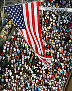 A giant American flag hangs above thousands of runners as their cross the start line of the annual Peachtree Road Race on July 4th in Atlanta.