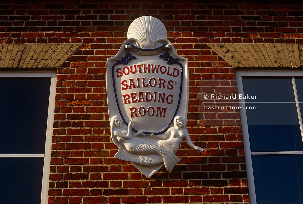 A detail of the ornate sign hanging outside the Sailor's Reading Room on East Cliff, Southwold, Suffolk. Topless mermaids and a shell form part of the sign on a red brick wall of this Grade II listed Sailors' Reading Room, which still provides daily papers and a place to read them. Built in 1864 in memory of Captain Charles Rayley RN, a naval officer at the time of Trafalgar, the Reading Room was a refuge for fishermen and sailors. It provided a place to meet and receive religious instruction, away from the pubs, and somewhere to read things that were good for the soul. Displays of a seafaring nature line the walls and fill glass cabinets. Pictures and portraits of local fishermen and seascapes, model ships and maritime paraphernalia offer a fascinating history of Southwold's connections with the sea.