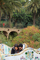 A couple look intently at their smartphone while visiting the Park Guell in Barcelona, Spain