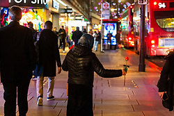 A woman in a headscarf sells roses to passersby on Oxford Street. Homeless Britons are coming under increasing pressure as a surge of Roma beggars from Romania arrive on the streets of London to take advantage of the generosity of Christmas shoppers. London, December 04 2018.