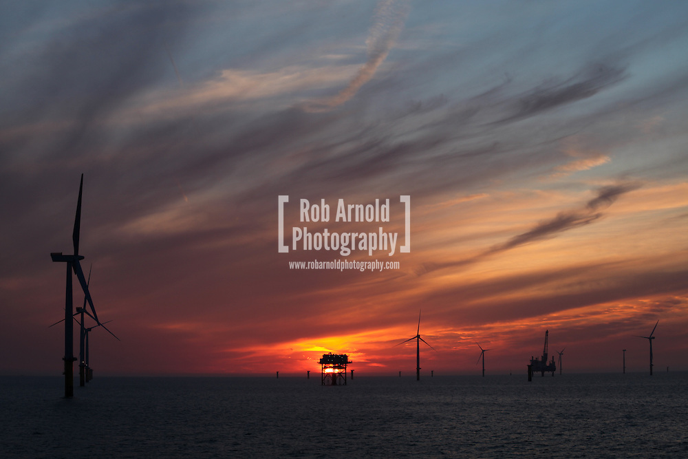 © Rob Arnold.  01/04/2014. North Wales, UK. A bright orange sky at sunset over the Gwynt y Môr Offshore Wind Farm off the coast of North Wales. Photo credit : Rob Arnold