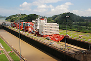 El Canal de Panamá mide aproximadamente 80 kilómetros de largo, de aguas profundas a aguas profundas, entre el Atlántico y el pacífico. Fue excavado a través de uno de los lugares más estrechos y de la parte más baja del montañoso Istmo que une a Norte y Sur América..Es un canal de esclusas. Las esclusas funcionan como elevadores de agua, que elevan las naves del nivel del mar (ya sea pacífico o del Atlántico) al nivel del Lago Gatún (26 metros sobre le nivel del agua), para permitir el cruce por la Cordillera Central, y luego bajarlos al nivel del mar al otro lado del Istmo. .Por cada buque que transita el Canal se usan unos 197 millones de litros de agua dulce, los cuales fluyen por gravedad a través de las esclusas y se vierten al océano..El Canal funciona 24 horas al día, 365 días al año, ofreciendo servicio de tránsito a naves de todas las naciones sin discriminación alguna.©Rafael Guillen / Istmophoto.com