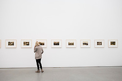 woman looking at photographs by Boris Mikhailov at Pinakothek Museum in Munich Germany