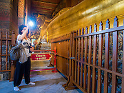 15 OCTOBER 2014 - BANGKOK, THAILAND: A European tourist photographs the Reclining Buddha in Wat Pho in Bangkok. The number of tourists arriving in Thailand in July fell 10.9 per cent from a year earlier, according to data from the Department of Tourism. The drop in arrivals is being blamed on continued uncertainty about Thailand's political situation. The tourist sector accounts for about 10 per cent of the Thai economy and suffered its biggest drop in visitors in June - the first full month after the army took power on May 22. Arrivals for the year to date are down 10.7% over the same period last year.   PHOTO BY JACK KURTZ