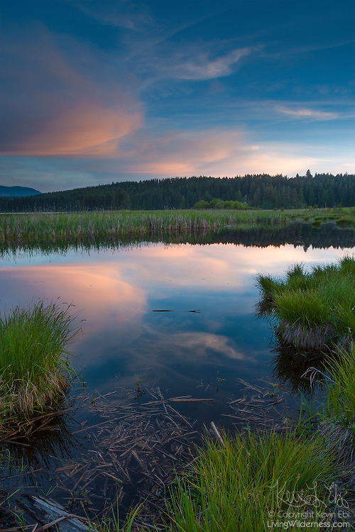 The setting sun colors wispy cirrus clouds that reflect in an unnamed lake in Sagle, Idaho.