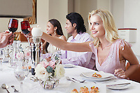 Young woman in dress toasting at formal dinner party