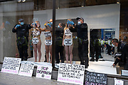 Police officers unglue the hands of environmental and Climate Change group Extinction rebellion supporters, protesting against the ethics of the fashion industry outside H&M on Oxford Street, on 9th September 2020, in London. XR say that the fashion industry produces around 10% of all humanity's carbon emissions, more than all international flights and maritime shipping combined and that over 800,000 tonnes of discarded textile waste annually in the UK.