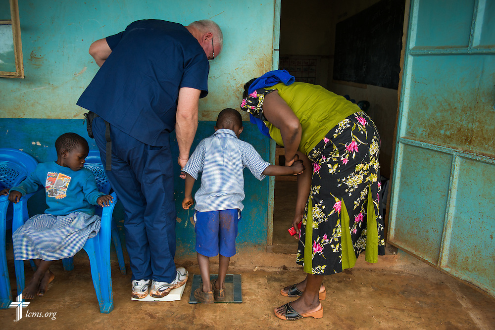Tom Andrews of Wentzville, Mo., attending Immanuel Lutheran Church, shows a boy how to weigh himself as he works in the intake area of the Mercy Medical Team clinic on Tuesday, June 10, 2014, at the Luanda Doho Primary School in Kakmega County, Kenya. LCMS Communications/Erik M. Lunsford