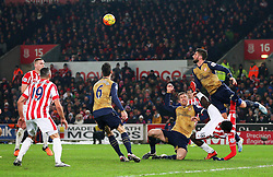 Arsenal's Olivier Giroud clears the ball ahead of Mame Biram Diouf of Stoke City  - Mandatory byline: Matt McNulty/JMP - 17/01/2016 - FOOTBALL - Britannia Stadium - Stoke, England - Stoke City v Arsenal - Barclays Premier League