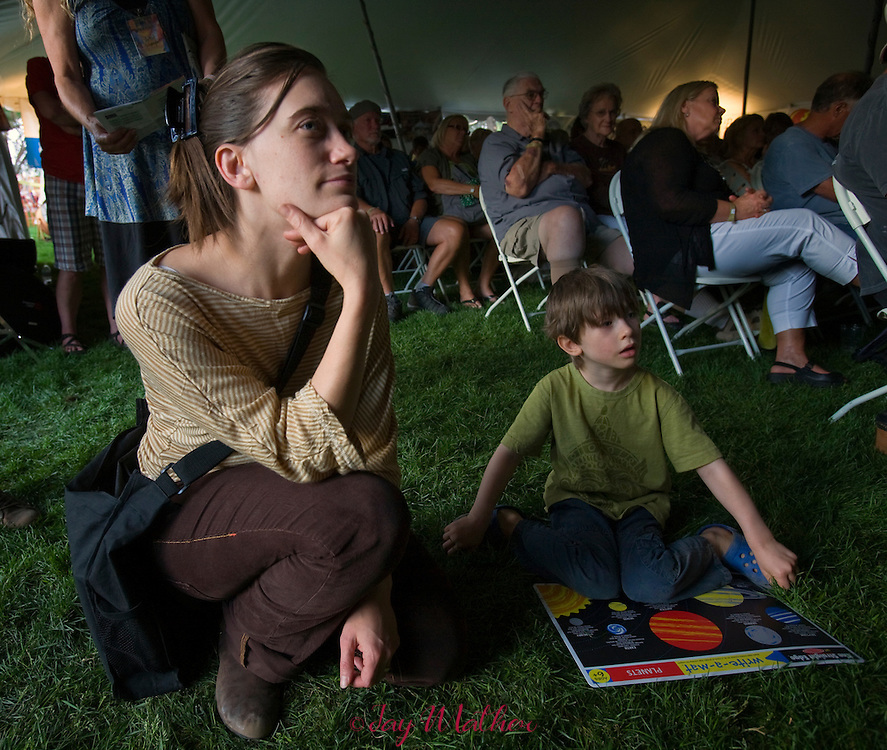 Enion Petta Tiller, the violinist in the group Taarka, sits with her son Aesop at the Village Green Community Celebration concert.
